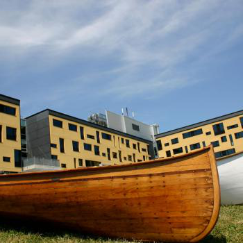 boats on the grass in front of the college building