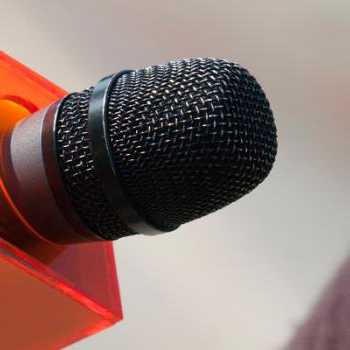Microphone being held with orange square collar on it