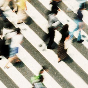 Birds eye view of people walking on a busy sidewalk. The people are blurred