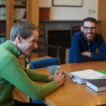 2 students and a professor sitting around a wooden table smiling and having a discussion