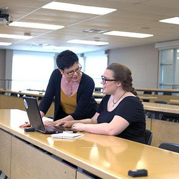 Faculty helping student in classroom